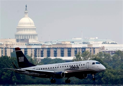With the Capitol in the background, a US Airways airplane makes its final approach at Ronald Reagan Washington National Airport, Thursday, Aug. 2, 2012. (AP Photo/Haraz N. Ghanbari)