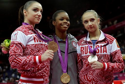 U.S. gymnast and gold medallist Gabrielle Douglas, center, Russian gymnast and silver medallist Victoria Komova, right, and Russian gymnast and bronze medallist Aliya Mustafina stand on the podium.