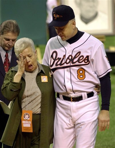 In this Oct. 6, 2001 file photo, Vi Ripken, mother of Cal Ripken of the Baltimore Orioles, wipes her eye while being escorted by her son after throwing out the ceremonial first pitch before Cal's final game.