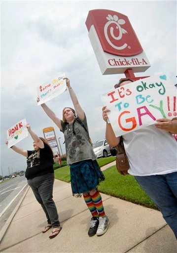 Gay marriage supporters, from left, Emmie Hesley, Cathy Dear and Amy Paffenroth hold signs in front of a Chick-fil-A in Fort Walton Beach, Fla.