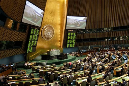 A hand is shown on a video screen, pushing a button to vote on a Saudi Arabian-sponsored draft resolution against Syria at the United Nations General Assembly at the United Nations, Friday, Aug. 3, 2012. (AP Photo/Kathy Willens)