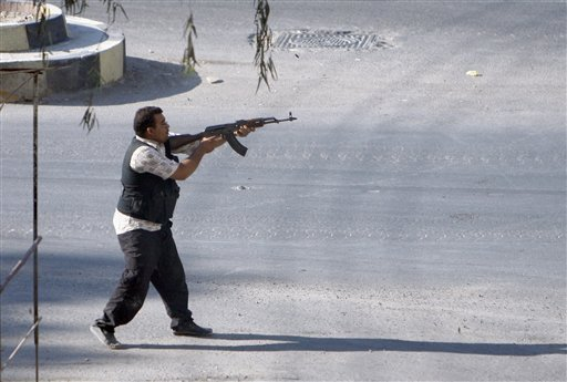 © In this Thursday Aug. 2, 2012 photograph, a Syrian rebel fighter fires at an approaching car at an improvised checkpoint in a suburb of Damascus, Syria.