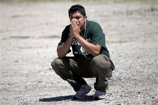 © A family member waits to hear information about his loved ones inside the Sikh Temple on S. Howell Avenue where a shooting occurred, Sunday, Aug. 5, 2012, in Oak Creek, Wis. (AP Photo/Milwaukee Journal-Sentinel, Mike De Sisti)