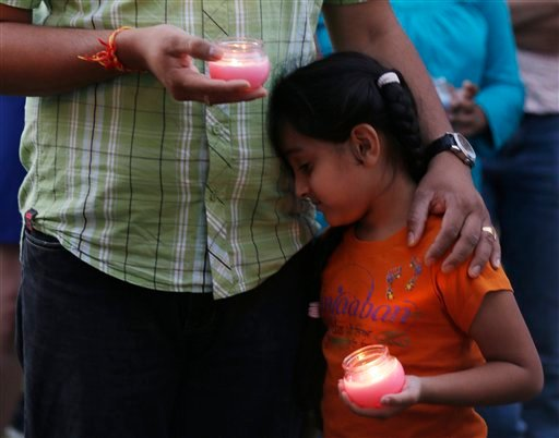© A man holds his child during a candle light vigil for the victims of the Sikh Temple of Wisconsin shooting in Milwaukee Sunday, Aug 5, 2012.