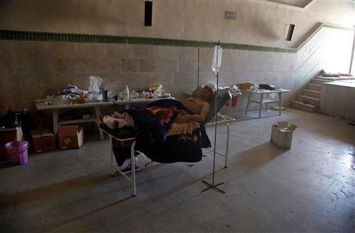 Mahmoud, a 21-year-old Palestinian resident of Syria, rests in a field hospital after he was found Monday, Aug. 6, 2012, with three gunshot wounds in the town of Anadan on the outskirts of Aleppo, Syria. (AP Photo)
