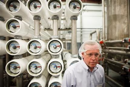 In this June 15, 2012 photo, Tim Gratto, Vice President of Sustainability, shows the massive water purification filters at the Dr. Pepper Snapple bottling plant in Houston. (AP Photo/Michael Stravato)