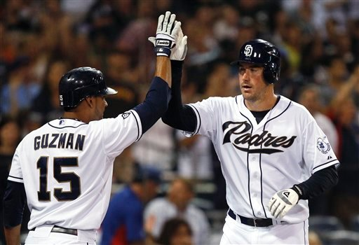 San Diego Padres pitcher Ross Ohlendorf high-fives with Jesus Guzman after scoring on a hit by Chase Headley in the third inning of a baseball game Aug. 7, 2012, in San Diego. (AP Photo/Lenny Ignelzi)