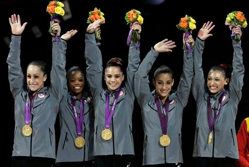 In this Tuesday, July 31, 2012, file photo, U.S. gymnasts,from left, Jordyn Wieber, Gabrielle Douglas, McKayla Maroney, Alexandra Raisman, Kyla Ross raise their hands on the podium during a medal ceremony.
