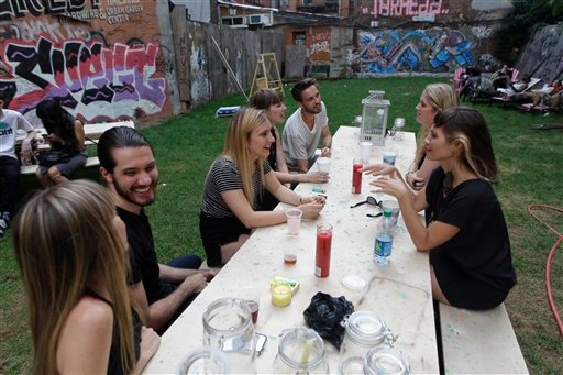 In this Wednesday, July 25 2012 photo, a group of people hang out at a picnic table at Timeshare Backyard on the Lower East Side of Manhattan. (AP Photo/Mary Altaffer)