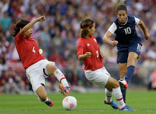 United States' Carli Lloyd (10) shoots past Japan's Saki Kumagai (4) and Azusa Iwashimizu (3) during the women's soccer gold medal match at the 2012 Summer Olympics, Thursday, Aug. 9, 2012, in London. (AP Photo/Ben Curtis)
