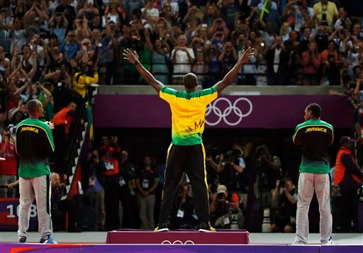 Jamaica's Usain Bolt, center, celebrates before receiving his gold medal as he stands alongside silver medallist Yohan Blake of Jamaica, right, and bronze medallist Warren Weir of Jamaica. (AP Photo/Matt Dunham)
