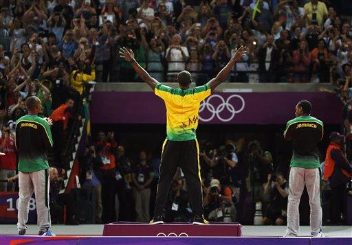 Jamaica's Usain Bolt, center, celebrates before receiving his gold medal as he stands alongside silver medallist Yohan Blake of Jamaica, right, and bronze medallist Warren Weir of Jamaica. (AP Photo/Matt Dunham)