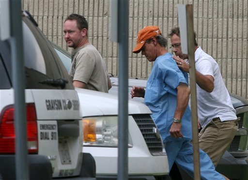 Randy Travis, center wearing cap, exits the Grayson County jail with two unknown persons Wednesday Aug. 8, 2012, in Sherman, Texas, after being arraigned on charges of driving while intoxicated and retaliation. (AP Photo)