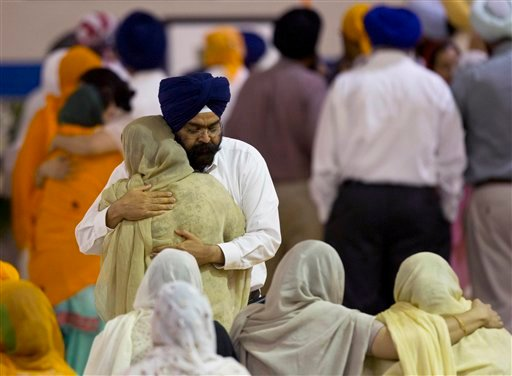 Mourners provide comfort Friday, Aug. 10, 2012 at the funeral and memorial service held in the Oak Creek High School for the six victims of Sunday's mass shooting at the Sikh Temple of Wisconsin in Oak Creek, Wis. (AP Photo/Jeffrey Phelps)
