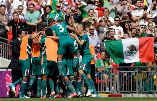 © Mexico players celebrate a goal by teammate Oribe Peralta during the men's soccer final against Brazil at the 2012 Summer Olympics, Saturday, Aug. 11, 2012, in London. (AP Photo/Hassan Ammar)