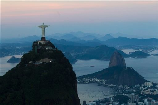 © FILE - In this May 10, 2012 file photo, the Christ the Redeemer statue stands back dropped by Sugar Loaf mountain, right, as the sun sets in Rio de Janeiro, Brazil.