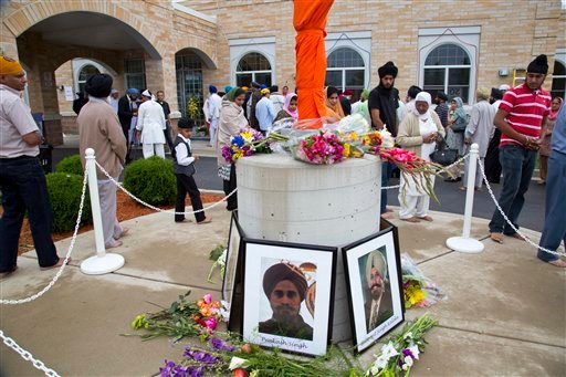 © People walk around a flag pole outside the Sikh Temple of Wisconsin in Oak Creek, Wis., Sunday, Aug. 12, 2012. More than 100 people gathered for the first Sunday prayer service since a white supremacist shot and killed six people.