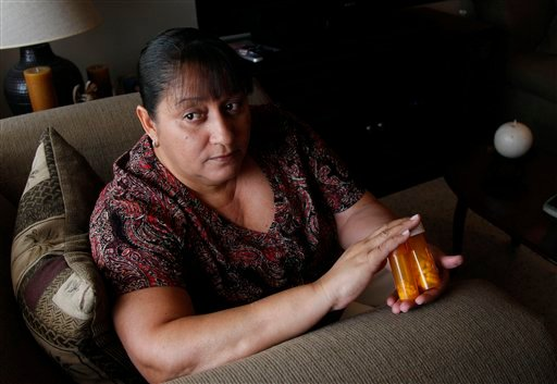In a Thursday, July 26, 2012 photo, Sandra Pico, 52, holds medications she takes, at her home in North Miami Beach, Fla. (AP Photo/Lynne Sladky)
