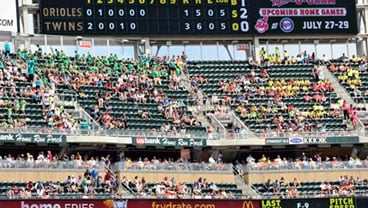 In this July 19, 2012, photo, fans watch a baseball game between the Baltimore Orioles and Minnesota Twins in Minneapolis. (AP Photo/Jim Mone)