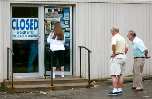 This Sept. 12, 2003 photo shows customers outside the Union Family Pharmacy in Dubuque, Iowa, after it was closed by federal agents that found evidence it had illegally dispensed drugs on the Internet. (AP Photo/Telegraph Herald, Dave Kettering)