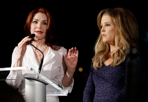 Priscilla Presley, left, and Lisa Marie Presley speak to fans gathered at a candlelight vigil at Graceland, Elvis Presley's Memphis, Tenn. home, on Wednesday, Aug. 15, 2012. (AP Photo/Mark Humphrey)