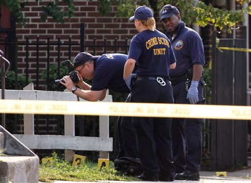 © Police investigate the crime scene after an off-duty Philadelphia police officer was shot and killed, Saturday, Aug. 18, 2012, in North Philadelphia.