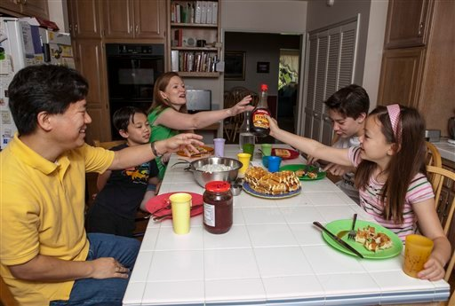 © In this photo taken Tuesday, Aug. 14, 2012, David Oh, a flight director of NASA's latest Mars mission, far left and his family have breakfast at 3 pm at their home in La Canada Flintridge, Calif.