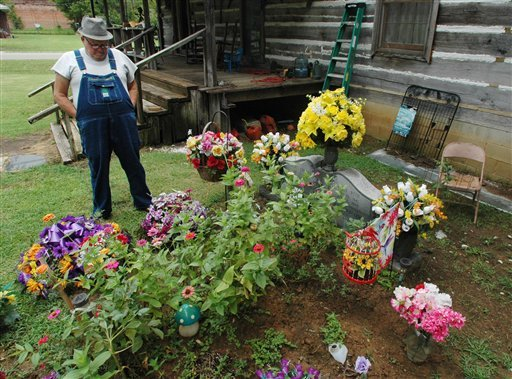 © In this Friday, Aug. 10, 2012 photo, James Davis, 73, stands over the grave of his wife, Patsy, in the front yard of the home they shared in Stevenson, Ala.