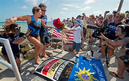 In this photo provided by the Florida Keys News Bureau, endurance swimmer Diana Nyad is helped to shore and a welcome from her team after swimming a short distance from a support boat Tuesday, Aug. 21, 2012, in Key West, Fla. (AP Photo)