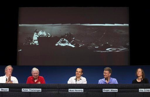 NASA scientists show a panoramic image of the Curiosity touch-down area Bradbury Landing, named after writer Ray Bradbury, showing the first tracks of the rover movements, at the Jet Propulsion Laboratory in Pasadena, Calif., Wednesday, Aug. 22, 2012.(AP)
