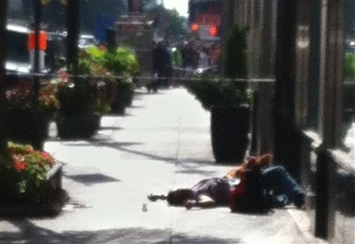 A body lies on the sidewalk near the Empire State Building after a shooting, Friday, Aug. 24, 2012, in New York.