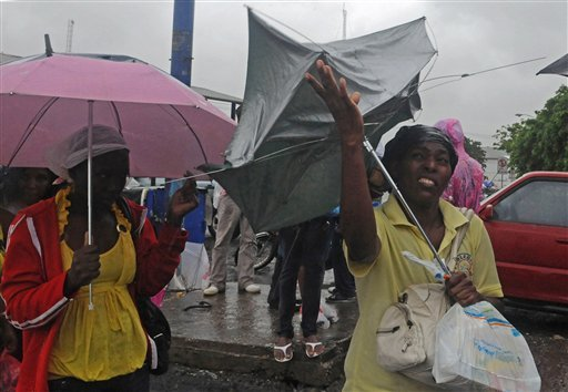 A woman struggles with her umbrella due to the wind as Tropical Storm Isaac affects Santo Domingo, Dominican Republic, Friday, Aug. 24, 2012. (AP Photo/Manuel Diaz)