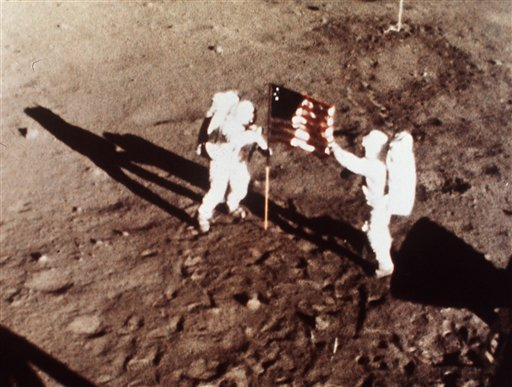 """© FILE - In this July 20, 1969 file photo provided by NASA shows Apollo 11 astronauts Neil Armstrong and Edwin E. """"Buzz"""" Aldrin, the first men to land on the moon, plant the U.S. flag on the lunar surface."""