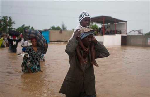 © A man carries a child as residents leave an area flooded by Tropical Storm Isaac in Port-au-Prince, Haiti, Saturday, Aug. 25, 2012.