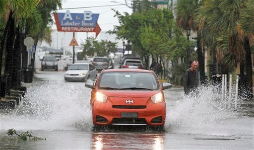 © A car goes through a flooded street due to heavy rains in Key West, Fla., Sunday, Aug. 26, 2012 as heavy winds and rain hit the northern coast.