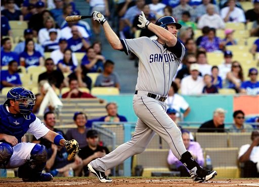 San Diego Padres' Chase Headley, right, hits a two-run home run as Los Angeles Dodgers catcher A.J. Ellis watches during the first inning of their baseball game, Monday, Sept. 3, 2012, in Los Angeles. (AP Photo/Mark J. Terrill)