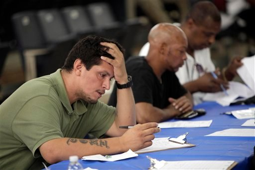 In this Tuesday, Aug. 21, 2012 file photo, job seekers fill out applications at a construction job fair in New York. (AP Photo/Seth Wenig, File)