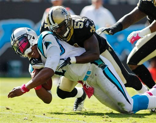 In this Oct. 9, 2011, photo, Carolina Panthers' Cam Newton, left, is tackled by New Orleans Saints' Jonathan Vilma (51) during an NFL football game in Charlotte, N.C. (AP Photo/Bob Leverone)
