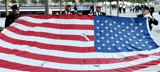 © Police officers of the Port Authority of New York and New Jersey, carry an American flag that flew over at the World Trade Center towers, during the 11th anniversary ceremonies at the site of the World Trade Center, in New York, Tuesday Sept. 11, 2012.