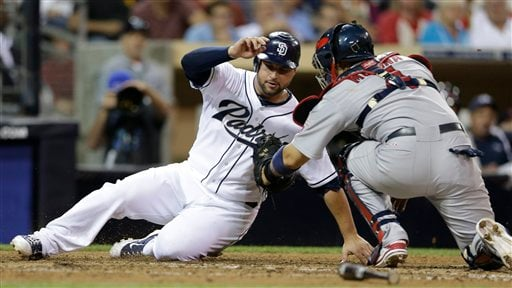 San Diego Padres' Yonder Alonso, left, is tagged out by St. Louis Cardinals catcher Yadier Molina, right, during the fourth inning of their baseball game, Tuesday, Sept. 11, 2012, in San Diego. (AP Photo/Gregory Bull)