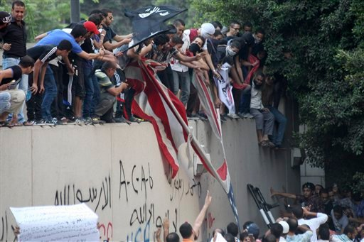 Protesters destroy an American flag pulled down from the U.S. embassy in Cairo, Egypt, Tuesday, Sept. 11, 2012.