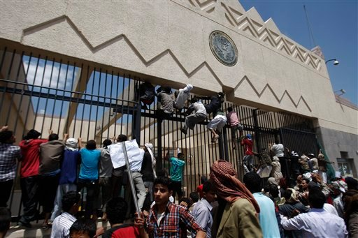 Yemeni protesters climb the gate of the U.S. Embassy during a protest about a film ridiculing Islam's Prophet Muhammad, in Sanaa, Yemen, Thursday, Sept. 13, 2012. (AP Photo/Hani Mohammed)