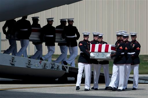 Carry teams move flag draped transfer cases of the remains of the four Americans killed this week in Benghazi, Libya, from a transport plane during the Transfer of Remains Ceremony, Friday, Sept. 14, 2012, at Andrews Air Force Base, Md. (AP Photo)