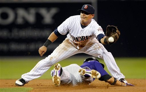 © San Diego Padres shortstop Everth Cabrera can't handle the throw, as Colorado Rockies' Carlos Gonzalez, below, steals second base during the seventh inning of their baseball game in San Diego, Calif., Friday, Sept. 14, 2012.
