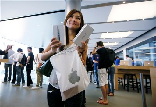A customer shows her new iPhone 5 at the Apple store in Hong Kong Friday, Sept. 21, 2012. Apple's Asian fans jammed the tech juggernaut's shops in Australia, Hong Kong, Japan and Singapore to pick up the latest version of its iPhone.