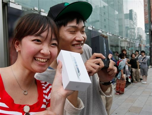 Kae Shibata 20, left, and Yutaro Noji, 21, show off Apple's iPhone 5 after they bought at a store in Tokyo Friday morning, Sept. 21, 2012.