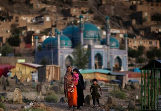An Afghan woman carries her child through the Kati Sakhi cemetery in Kabul, Afghanistan, Thursday, Sept. 20, 2012.