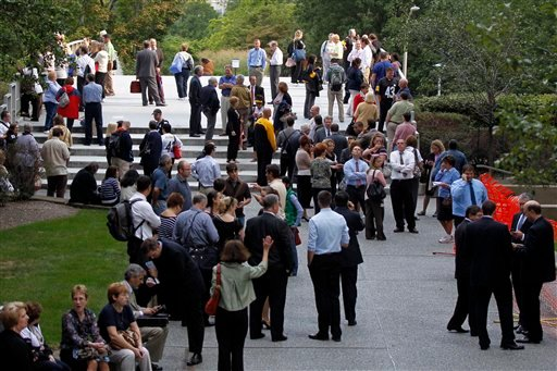 People evacuated by Pittsburgh Police from the Gateway Three office building wait outside as the police negotiate with a man who claims to have a bomb in a suite in the sixteenth floor, in downtown Pittsburgh Friday, Sept. 21, 2012.