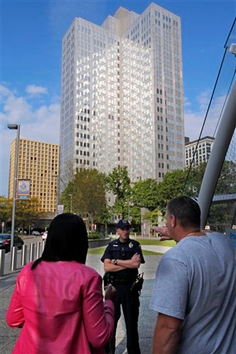 Police block off the area around Three Gateway Centeroffice building, rear, where they are negotiating with a man who claims to have a bomb, in downtown Pittsburgh Friday, Sept. 21, 2012.