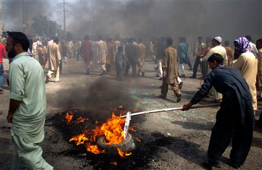 Pakistani protesters burn tires to block the main highway in Rawalpindi, Pakistan on Friday, Sept. 21, 2012.